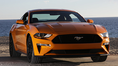 A yellow orange Mustang stands proudly in front of the blue ocean