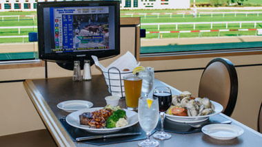 2 dinners on the table overlooking the racetrack